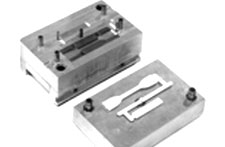 Two cavity, semi-automatic mold makes tensile and impact test specimens.